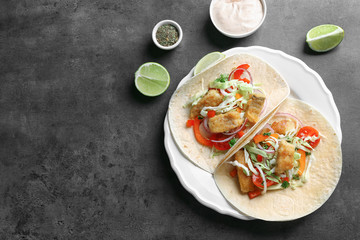Plate with tasty fish tacos on gray table