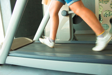 Fitness girl running on treadmill. Woman in gym