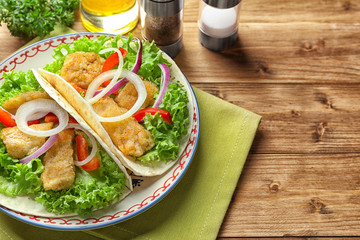 Plate with tasty fish tacos on wooden table
