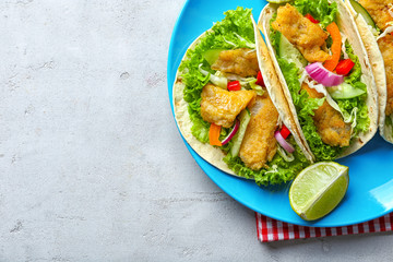 Plate with tasty fish tacos on table