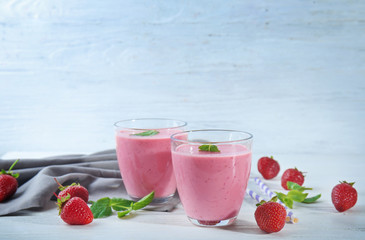 Glasses of fresh strawberry smoothie on wooden table