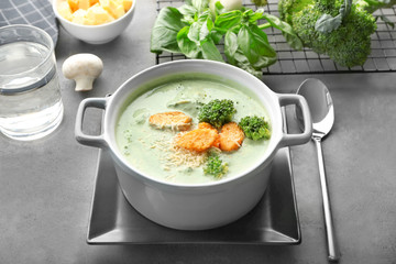 Dish with delicious broccoli cheese soup and croutons on table