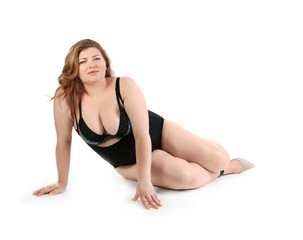 Overweight woman in beautiful underwear posing on white background