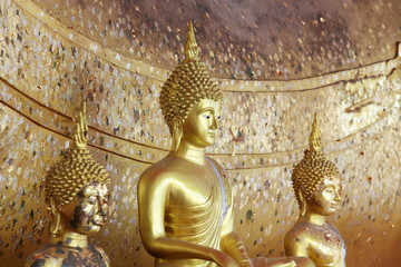 golden buddha statue with gold leaf background.