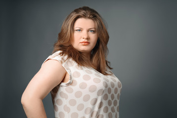 Overweight stylish woman on grey background