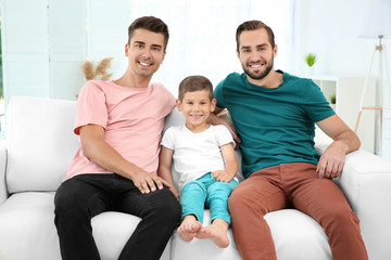Male gay couple with foster son sitting on sofa at home. Adoption concept