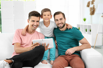 Male gay couple with foster son resting at home. Adoption concept