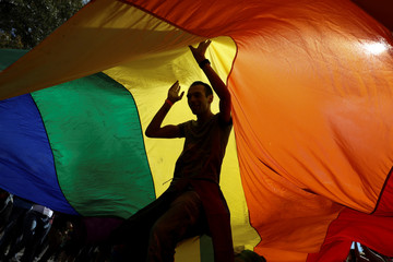 Participants dance under a rainbow flag during an annual LGBT pride parade in Belgrade