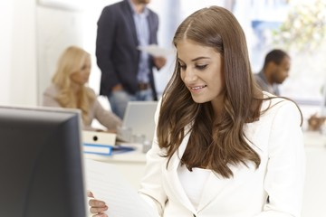 Young woman working in busy office