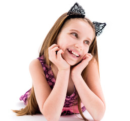 Cute teen girl wearing black laced ears of a cat, lying on the floor, smiling