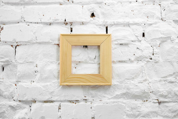 Square wooden frame on a white brick wall