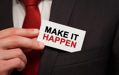 Businessman putting a card with text Make it happen in the pocket
