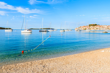 Fototapete - Beach with crystal clear sea water in Primosten town at early morning, Dalmatia, Croatia
