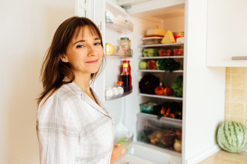 Young beautiful brunette woman in pajamas searching for food in the fridge and looking at camera.