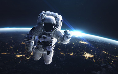 Astronaut at spacewalk. Earth at night, city lights from orbit. Elements of this image furnished by NASA