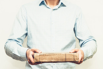 Man holding old rusty book in his hands. Staying in front of camera.