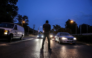 A peaceful protester stops traffic on Forest Park Parkway during the second day of demonstrations after a not guilty verdict in the murder trial of former St. Louis police officer Jason Stockley in St. Louis