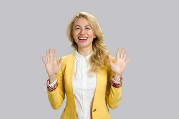 Joyful young woman gesturing stop. Happy smiling young business woman showing stop gesture with both hands isolated on grey background. Human facial expressions and body language.