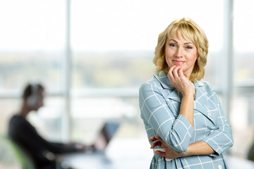 Portrait of attractive mature woman. Adult lady holding hand on chin and looking at camera while standing on office window background.