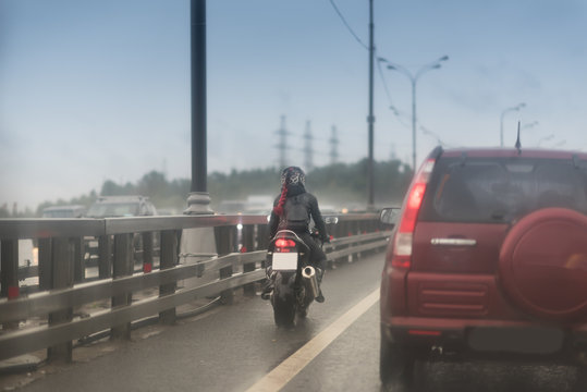 Girl with red hair in a helmet rides her motorcycle on the pavement on a rainy day.