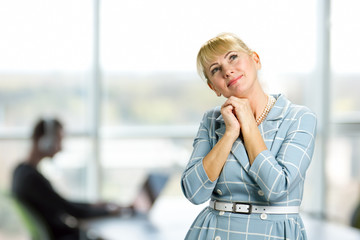 Portrait of thoughtful smiling mature woman. Middle aged woman clasped her hands under chin and looking upwards thinking and smiling on office window background.