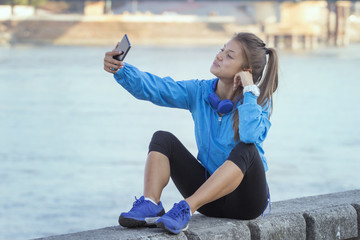 Young girl with headphones on her head resting after jogging and taking selfie by mobile phone