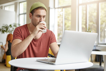 Young handsome hipster wears stylish clothes, drinks coffee at cafeteria, looks attentively in laptop computer, reads news online, has serious expression. Businessman relaxes after hard working day
