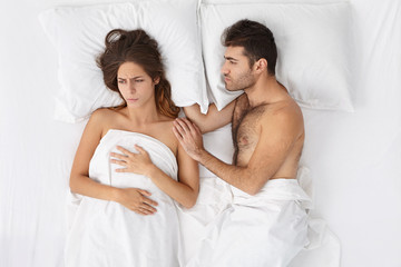 Bedtime, people, marriage, familyand relationhsips concept. Bearded man apologizing to angry woman in bed, saying sorry. Frustrated wife having headache, refusing to have sex with her husband