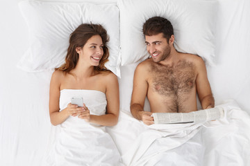 Happy loving couple in bedroom: bearded handsome man reads newspaper and his wife surfes social networking on smart phone using free internet before sleep, look at each other with great love