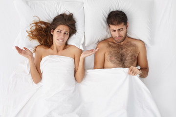 People, health problems, difficulties and crisis concept. Depressed couple have troubles, can`t recieve satisfaction in bed. Man has problem with impotence after stress, expreience erection failure