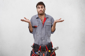 Studio shot of emotional clueless young unshaven male plumber with belt kit of working tools having confused puzzled look, shrugging shoulders as he doesn't know reason of leakage or accident