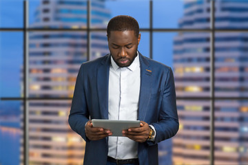 Handsome businessman holding computer tablet. Confident dark skinned manager looking down at digital tablet. Afro american executive with pc tablet on evening skyscraper background.