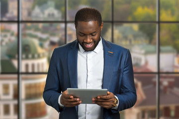 Smiling businessman with computer tablet. Black manager in formal wear on blurred background. Executive directo is reading news on computer tablet.
