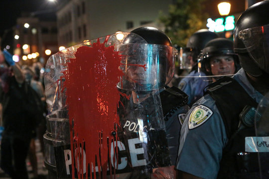 Red paint is splattered on the shield of a policeman during the second night of demonstrations after a not guilty verdict in the murder trial of former St. Louis police officer Jason Stockley in St. Louis