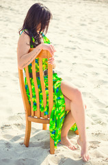 Beautiful woman on the sand in the desert in a green summer dress with patterns. Bright clothes and style for an all-day stylish look.