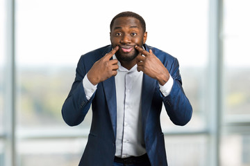 Black businessman with artificial smile. Businessman making a face at camera holding his fingers near lips.