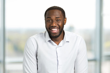 Wide smiling happy businessman. Cheerful black man in white shirt on blurred background.