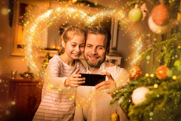 Christmas - father and daughter take 'selfie' photo on phone