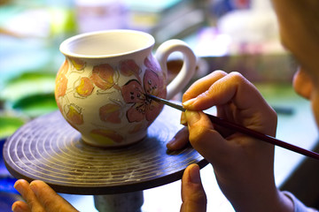 Woman working In her pottery studio. Ceramic workshop. Paint on clay mug in the pottery.