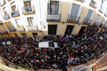 People gather outside a local theatre as they listen speech during a rally in favour of a planned referendum on the independence of Catalonia in Madrid
