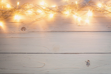 christmas background and lights garland on wood background with space.