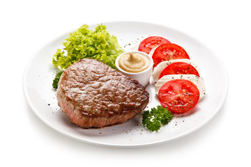 Grilled beef steak with mozzarella and vegetables on white background