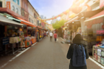 Backpack asian girl has traveling and shopping at China Town outdoor market with sunrise in the morning at Singapore.