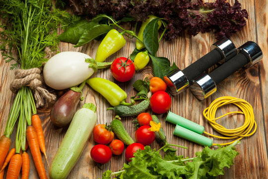 Fresh vegetables, sports, diet on a wooden background