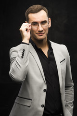 The young man in a gray suit and glasses on a dark background.