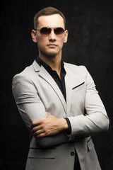 The young man in a gray suit and sunglasses on a dark background.