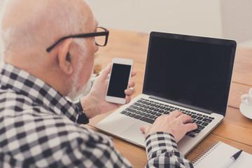 Senior man using laptop and smartphone mockup