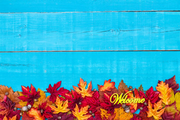 Welcome sign on rustic teal blue wood background with colorful autumn leaves border; fall sign with copy space