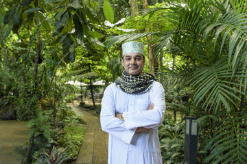 Portrait of smile handsome Arab muslim man in meshlah - white dress and prayer cap on head with red yashmagh on neck in half length and cross his arm standing in outdoor garden .
