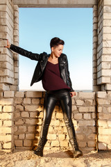 Young girl dressed in leather clothes, posing in abandoned building